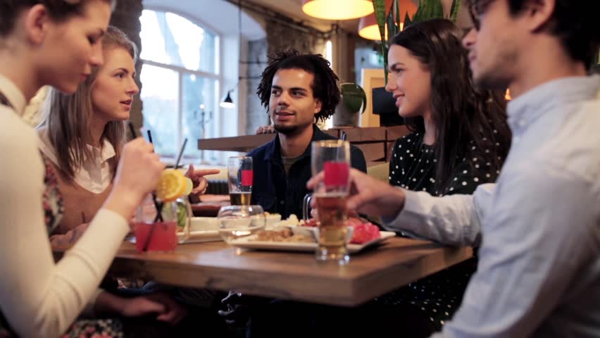 Leisure, food, drinks, people and holidays concept - happy friends eating and drinking at bar or cafe | Shutterstock HD Video #25606145