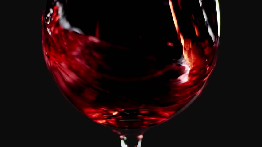 Filling wine glass with red wine super slow motion macro shot, black background