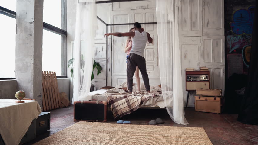 Young multiethnic couple in pajamas dancing, jumping on the bed. African boy and european woman have fun in the morning. | Shutterstock HD Video #25623185