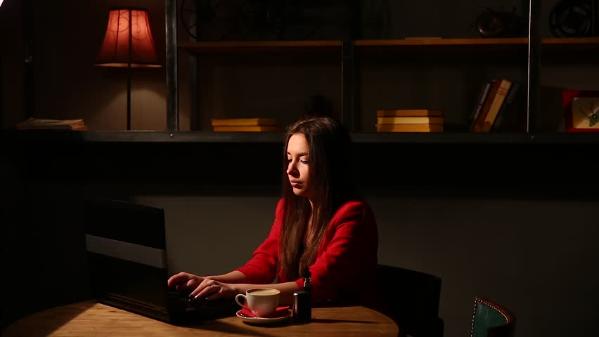 Girl working with laptop drinking coffee Smoking an electronic cigarette. Working remotely in a cafe. | Shutterstock HD Video #25627415