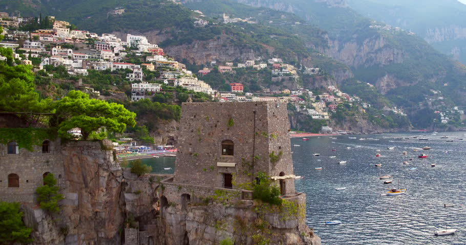Discovering Positano village aerial shot with boats in sea drone shot
