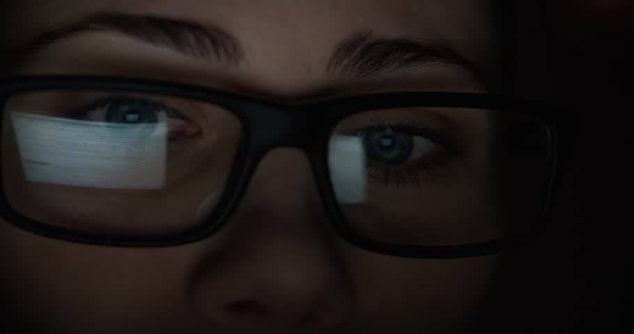 Woman with glasses eyes looking at the monitor, surfing the Internet, extreme close-up, dark room | Shutterstock HD Video #25638344