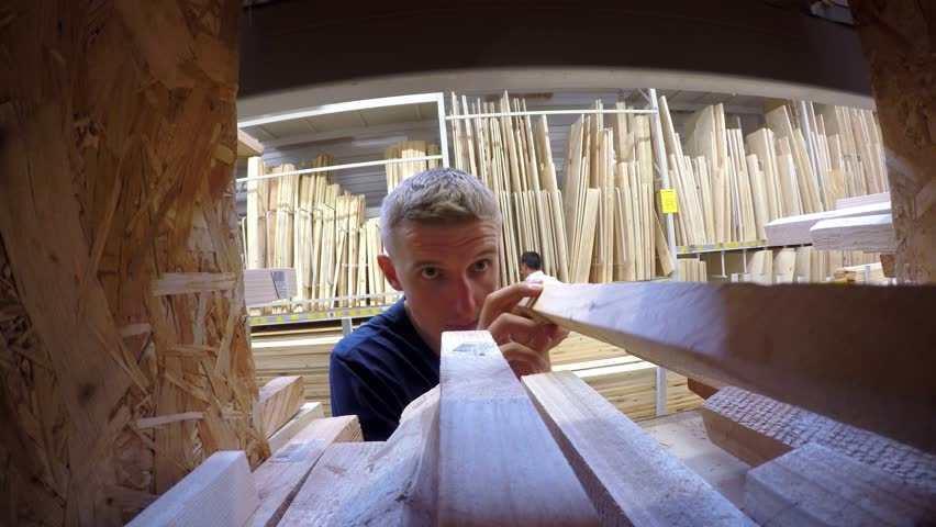 Man Choosing and Buying Construction Wood in DIY Store