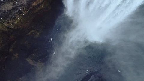 Aerial flight with drone over the famous  Skogar waterfall in Iceland. It is located on the South of the island. Image taken with action drone camera causing distortion and blur. Slow motion shot