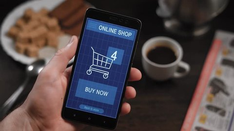 Shopping in an online store on your smartphone. The man has already chosen the goods, they are in the virtual basket, the finger presses the button to pay now, the transaction is successful.