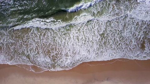 Aerial view of ocean waves crashing on beach, 4K drone footage.