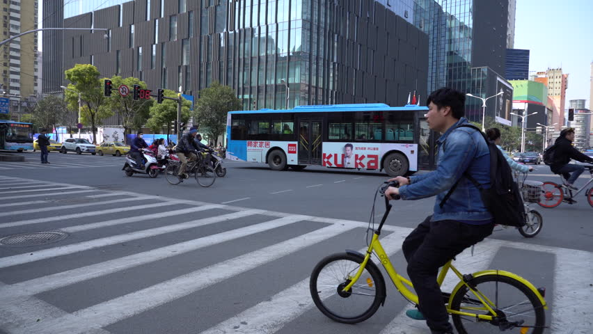 Mar.24,2017-Nanjing,China:People ride 'Ofo' share bike on the city road.  'Dockless' share bikes have flooded on the streets of Chinese cities,