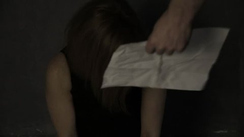 frightened crying girl gagged, kidnapper causes hostage to read the message to camera. linen bag on the head of a hostage. kidnapping and violence