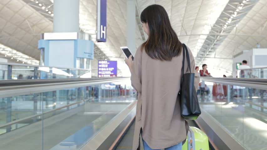 Back view of woman on travelator and using cellphone with her luggage at Hong Kong international airport  | Shutterstock HD Video #25729556