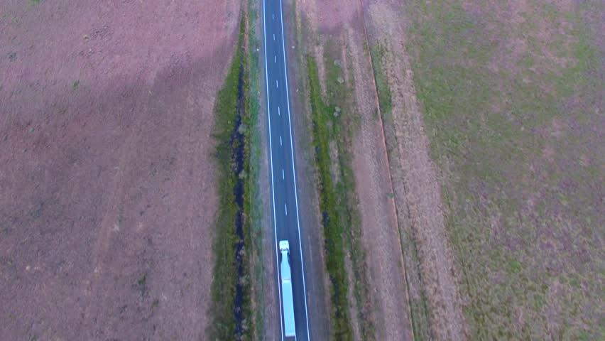 Aerial scene of truck on outback highway on dusk (sunset)