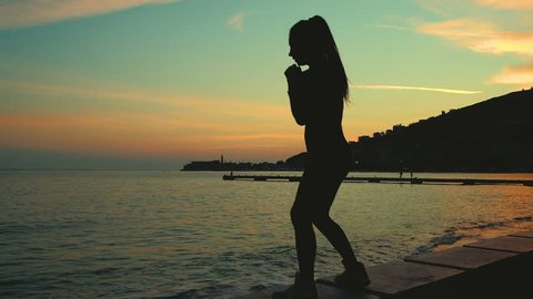 Athlete outline boxing into air on sea shore beach on sunset. Attractive female with pony tail hair hit with hands on lake, working out, do sports, mountains on background in the evening. Fit sporty