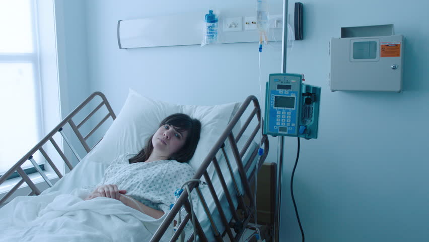 A sick young woman with an IV recovering in a hospital bed next to a window, slow motion, 4K | Shutterstock HD Video #25746650