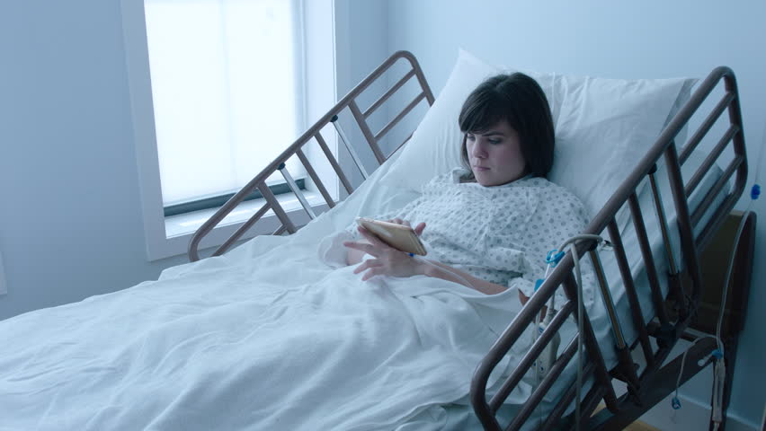 A sick young woman with an IV texting on a smartphone in a hospital bed next to a window, slow motion, 4K #25746665