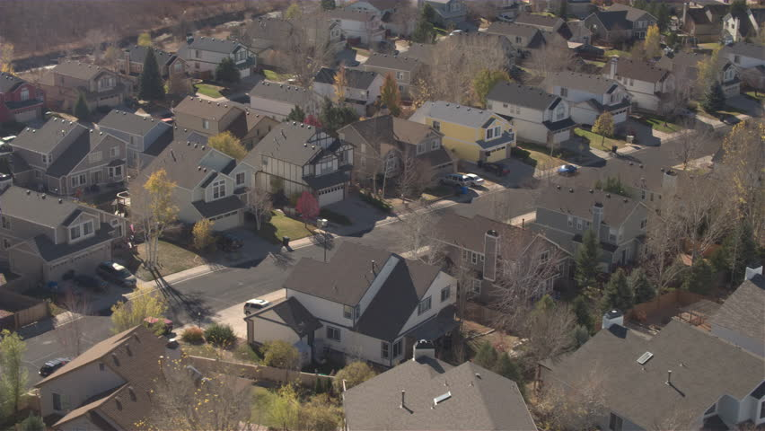 AERIAL, CLOSE UP: Flying close above the rooftops of beautiful idyllic wooden row houses in subdivision suburban town. Cars, pickup trucks and SUVs parked in frontyards and driveways in sunny city