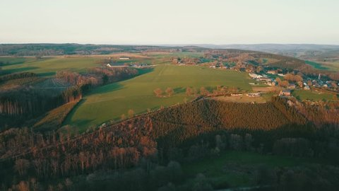 Aerial: Autumnal landscape of colorful trees in a valley in Belgian ardennes during sundown