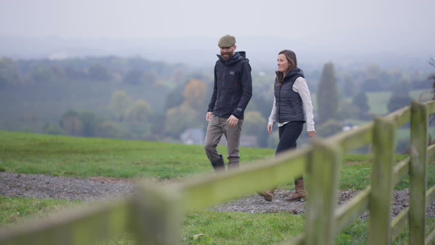 4K Farming couple walking in the field & checking on herd of cattle