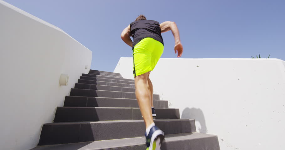 Running Stairs - man runner sprinting up staircase in HIIT run exercise. Fit male athlete exercising sprint up stairway. RED EPIC SLOW MOTION.
