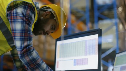 Male Inspector Wearing Hard Hat Fills in Spreadsheets on His Personal Computer. He's in Big Warehouse with Rows of Pallet Racks. Shot on RED EPIC-W 8K Helium Cinema Camera.