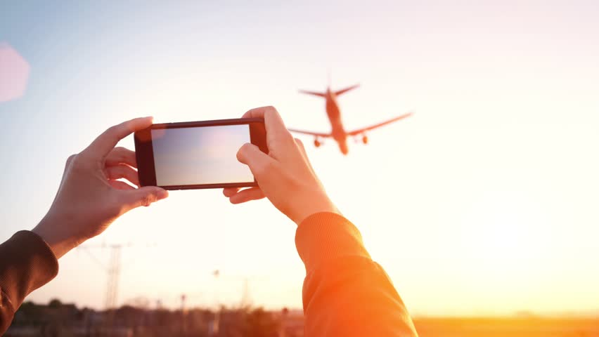 Cinemagraph of woman hands holding smart phone and taking video of big airplane landing in international airport hub at sunset time