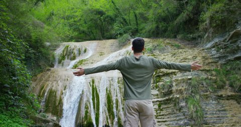 Happy young man, breathes in himself a breath of air to transform the qi, feels free and independent , on the background of a beautiful waterfall and rocks, concept: nature, religion, bio, ecology.