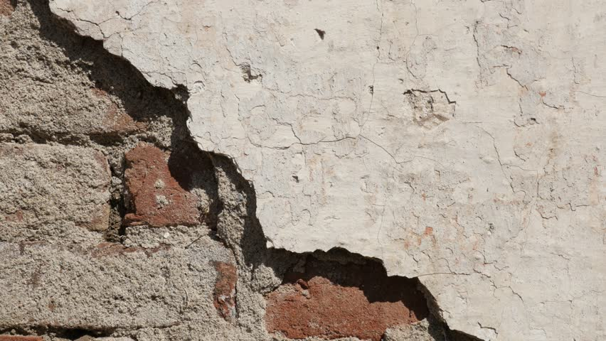 Close-up of destroyed building facade 4K 2160p 30fps UltraHD tilting footage - Brick wall and remains of white cement plaster slow tilt 3840X2160 UHD video