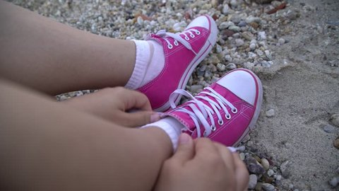 Close up shot of young Caucasian hipster girl s feet in pink snickers on  sea beach. 93c9d3cd6