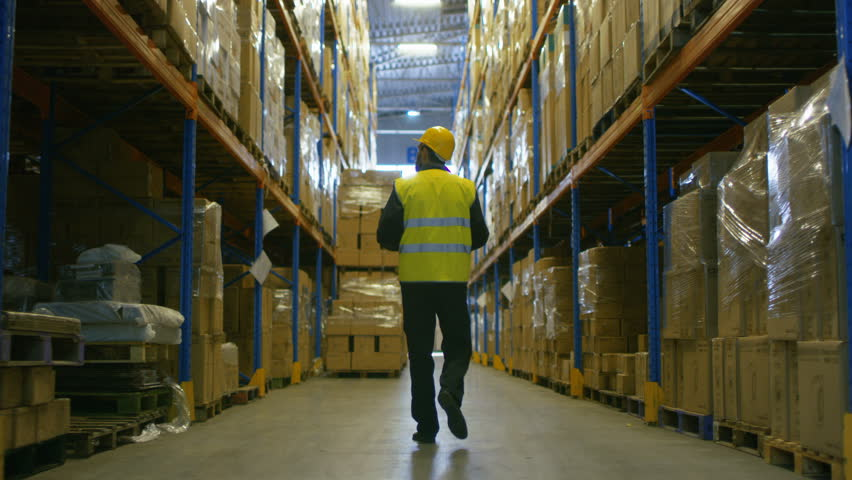Following Shot of a Warehouse Worker Wearing Hard Hat Walking Through Rows of Storage Racks. Shot on RED EPIC-W 8K Helium Cinema Camera.