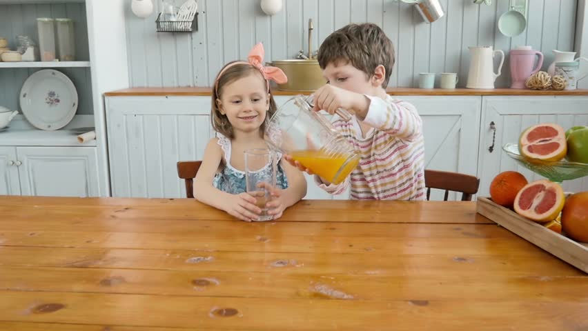 Boy Brother Serving Orange Juice For Children Girl Sister In Kitchen Happy Family