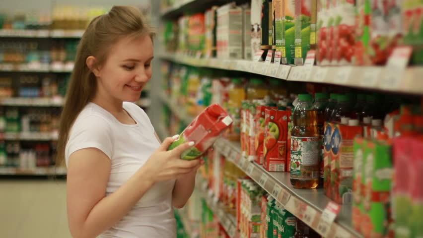 Pretty woman buys bottle fo apple juice at supermarket | Shutterstock HD Video #25863602