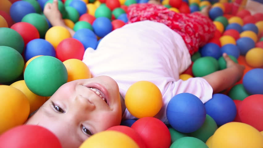 three year old boy in a pool of coloured balls
