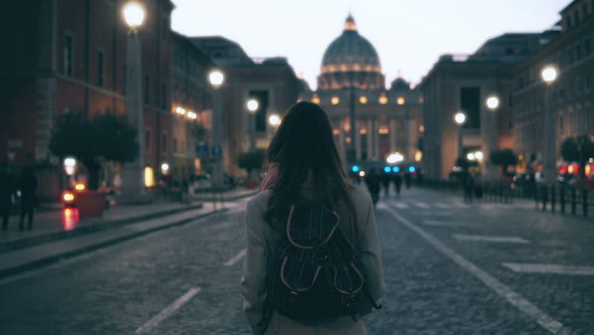Young tourist woman walking in Piazza di spagna near the Saint Peter Cathedral. Girl looking around, exploring sights.