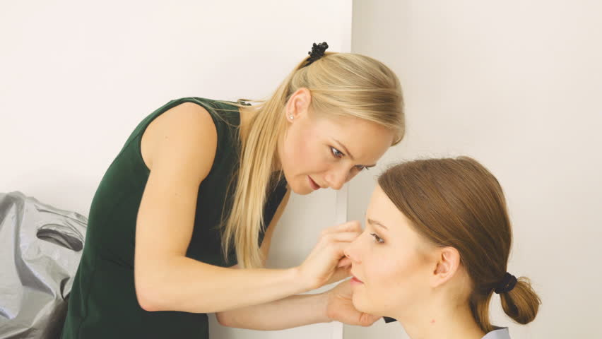 Specialist doing makeup for model. Gentle make-up for the young girl.