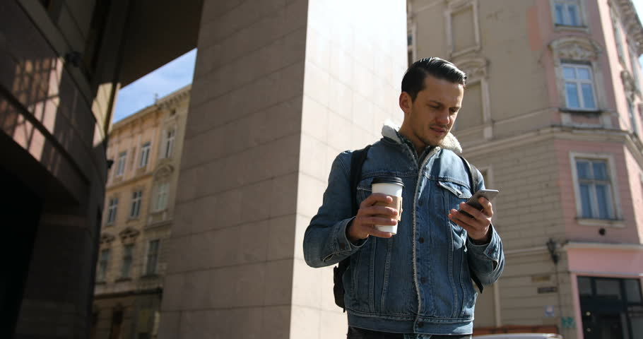 Attractive young man use phone and drinking coffee on the street in sunny spring day | Shutterstock HD Video #25902695