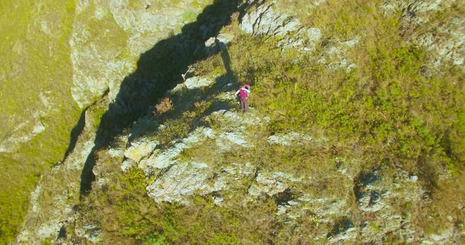 Aerial UHD 4K view. Orbital radial flight around young hiking man standing on top of the cliff at mountain meadow and rural road. Looks away. | Shutterstock HD Video #25909385