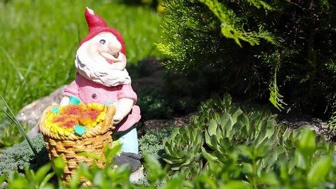 Gnome in a garden holding a basket