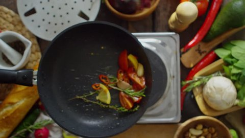 Top view of male hand holding frying pan and tossing up mixed vegetables in slow motion