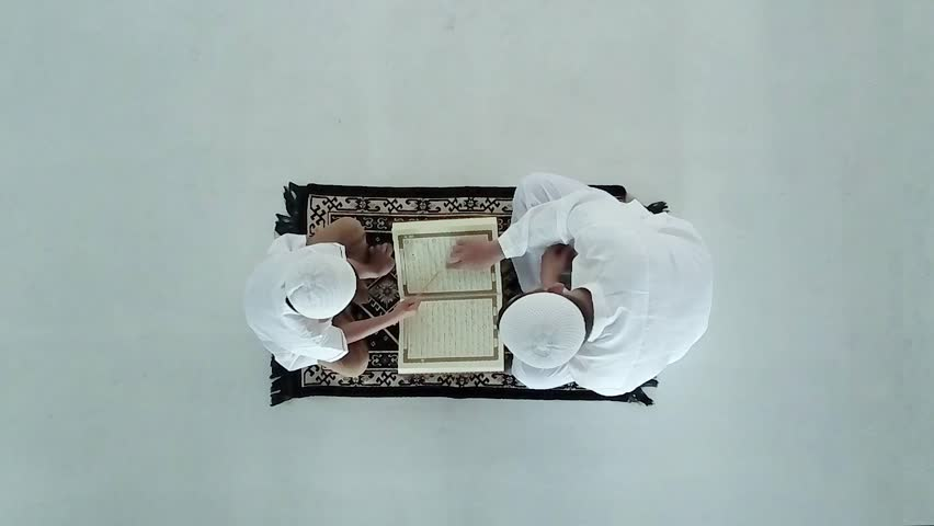 Video footage of top view of young muslim man teaching his son to read Koran, isolated on white background