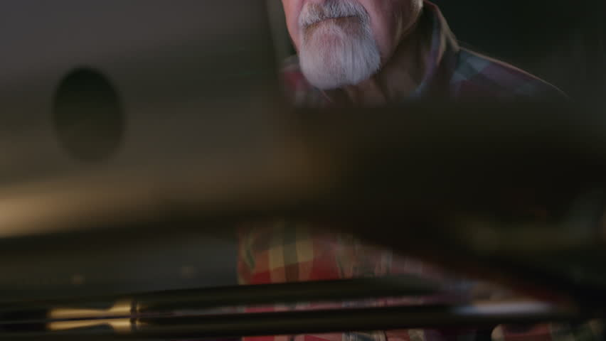 Close up low angle shot of older man using laptop / Cedar Hills, Utah, United States