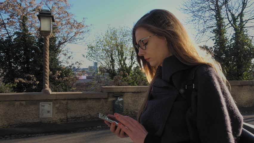 Young brunette woman with eyeglasses using smartphone outdoor. Walking and typing on the phone, taking a call and talking. Camera on gimbal moves with her. Spring time. | Shutterstock HD Video #25961615