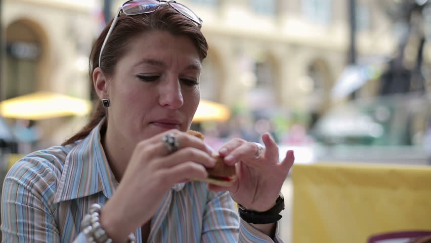 Woman eating sandwich, hamburger in bar  | Shutterstock HD Video #2599658