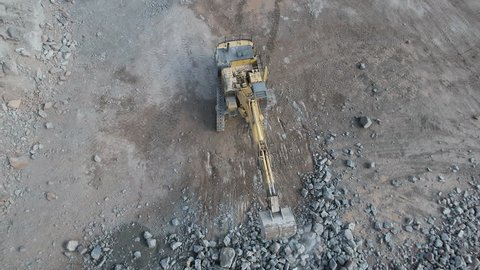 Rising Aerial View of a Digger Moving Freshly Blasted Rock in a Quarry