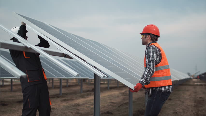 Two workers in a uniform and hardhat install photovoltaic panels on a metal basis on a solar farm | Shutterstock HD Video #26001845