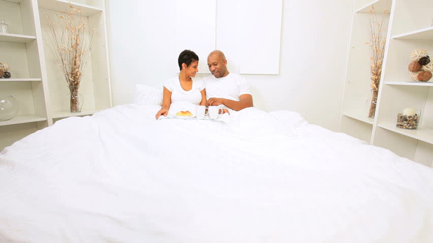 Ethnic heterosexual couple enjoying breakfast bed weekend