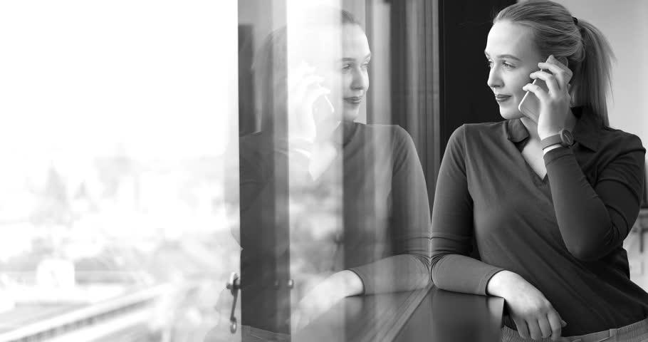 Elegant Woman Using Mobile Phone by window in office building | Shutterstock HD Video #26012345