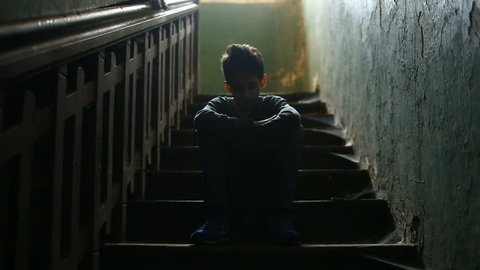 The boy is sitting on the steps of an abandoned porch. The concept of children's drug addiction, vagrancy, homelessness.