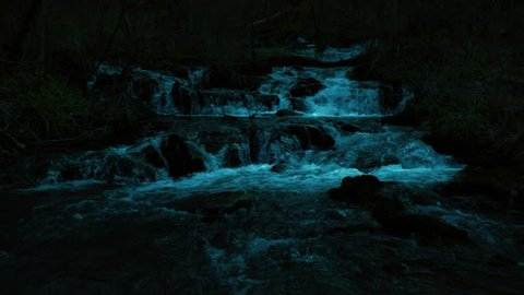 Beautiful cinematic night shot of the cascading waters at Mill Springs, Kentucky, near Monticello with moon light giving a glow to the beautiful waterfall churning up whitewater as it rolls at night.