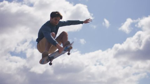 Skateboarder grabs his board in mid air during a jump, in slow motion