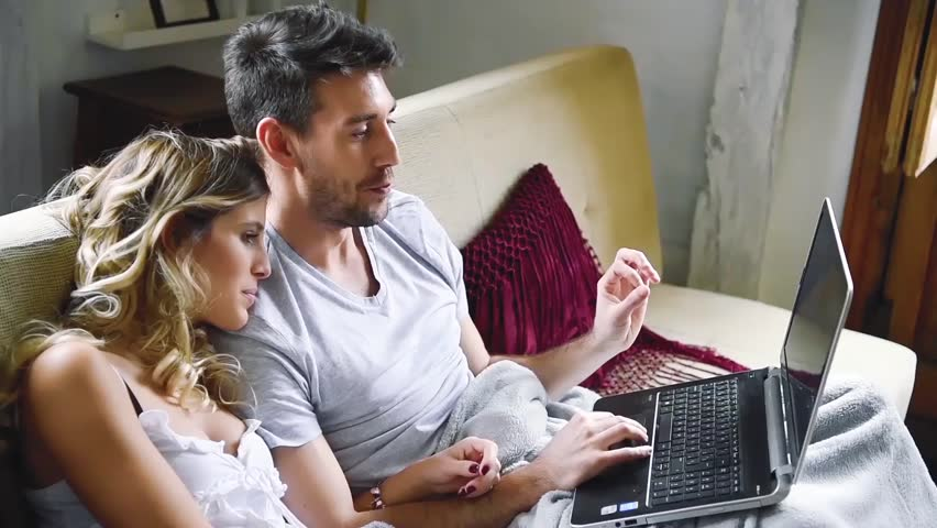 Young laughing couple using laptop while sitting on couch in apartment.  | Shutterstock HD Video #26041145