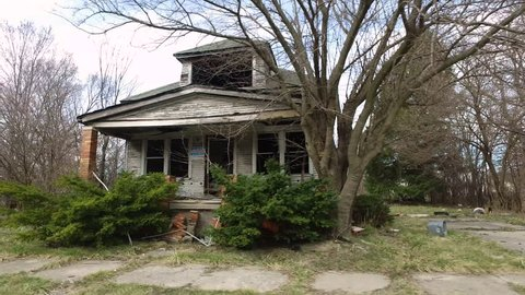 Driving shot moves by vacant lot to reveal blighted abandoned burned home. Use to show financial collapse or crisis, Detroit's bankruptcy, dangerous neighborhoods, hopelessness, rising from the ashes