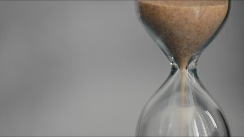 Hourglass on a gray background. The sand of yellow color is poured into the lower part of the clock. In the right part of the frame